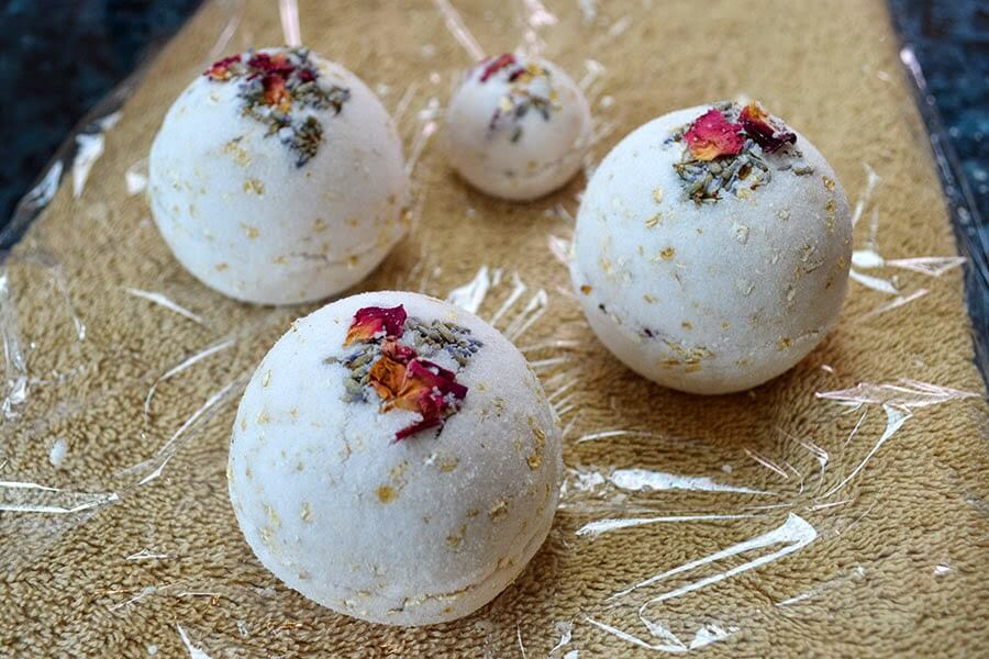 Learn how to make handmade bath bombs with a secret cache of rose petals and lavender. They float out as the bath bomb dissolves in warm water #diybath #diybeauty #essentialoils #roses