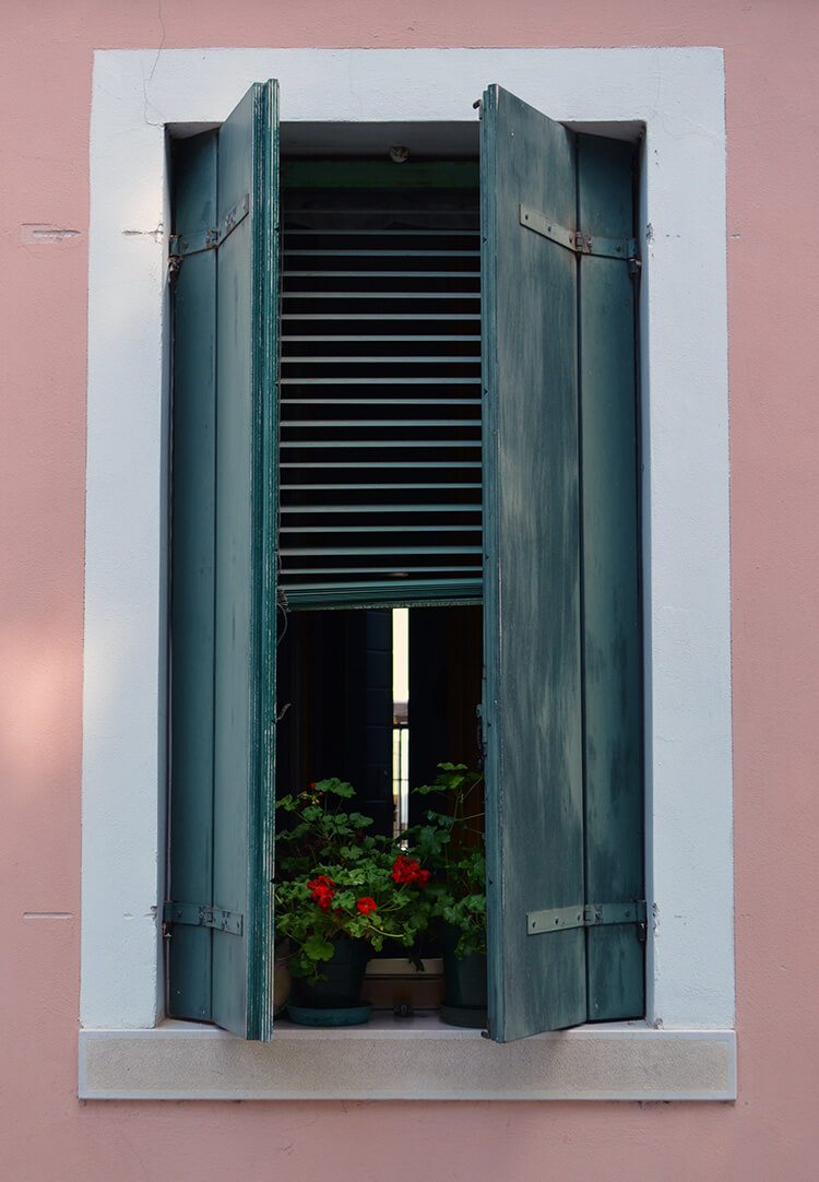 Geraniums in a window. Photo diary of a solo trip to Venice, Italy, one of the most romantic cities in the world.