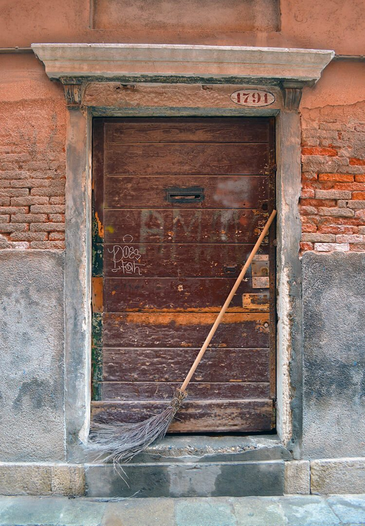Old door & broom. Photo diary of a solo trip to Venice, Italy, one of the most romantic cities in the world.