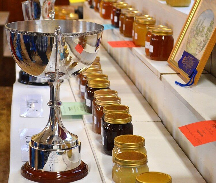 Beekeeping show on the Isle of Man featuring raw honey, beeswax, crafts, and honeybee-friendly flowers