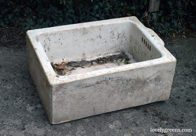 an old vintage sink sitting on the driveway. There are a few leaves inside and it's seen better days