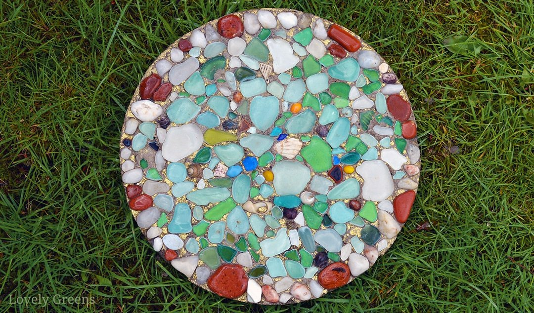 Make a colorful sea glass stepping stone for the garden using sea glass, marbles, or colored glass. This project requires only a few inexpensive materials including glass pieces. Full video included #seaglass #gardendiy #gardeningidea