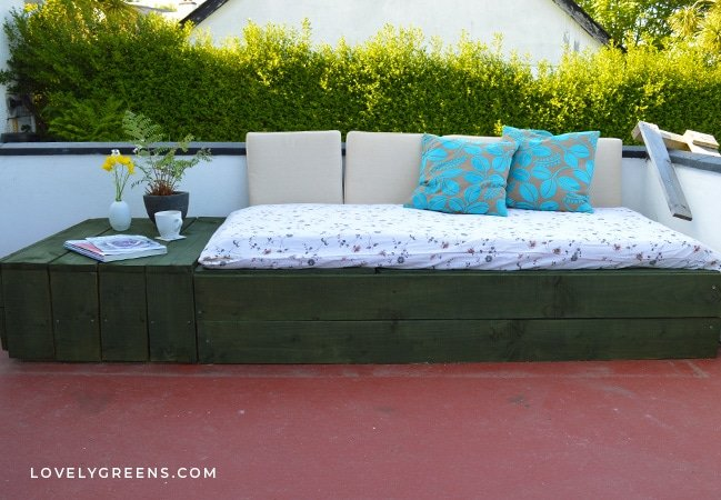 Create a patio day bed by stacking four wood pallets together and disguising them with wood facing. A simple and inexpensive outdoor seating project #pallet #diygarden #outdoorseating