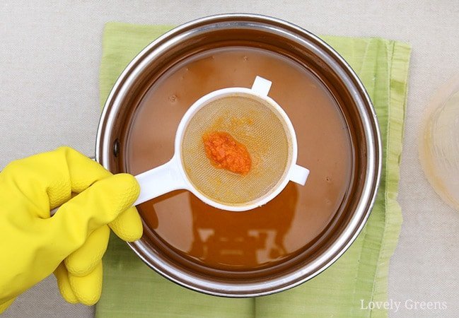 How to make carrot soap using real carrots: sieve the carrot lye solution as you pour it into the oils