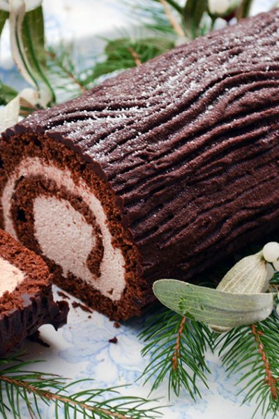 Delicious and chocolatey Yule Log Recipe to celebrate the holidays. It's a shallow cake that you spread with cream and then roll up and decorate for Christmas. It's simpler to make than you'd think and the perfect combination of chocolate and cream filling #christmascake #yule #buchedenoel #yulelog #cakerecipe